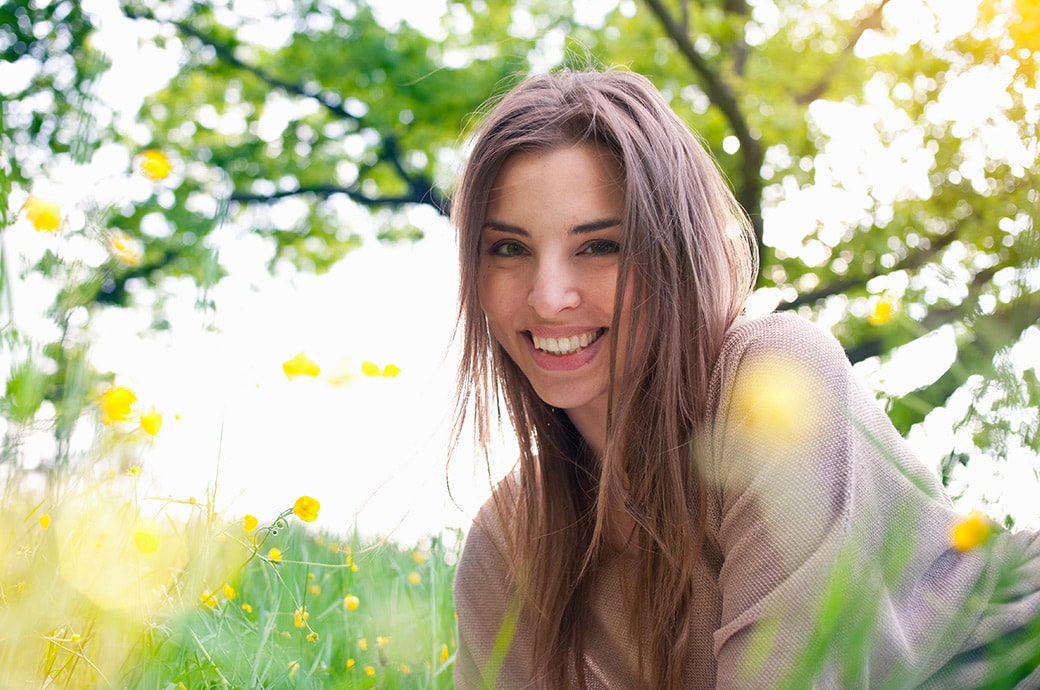 Adult woman smiling as she lays on the grass with the sun shiningMujer adulta sonriendo mientras descanza en la grama con el sol brillando