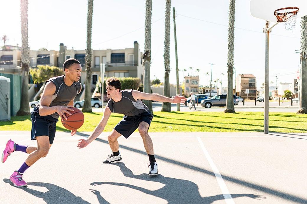Dos chicos jugando al baloncesto en el parque