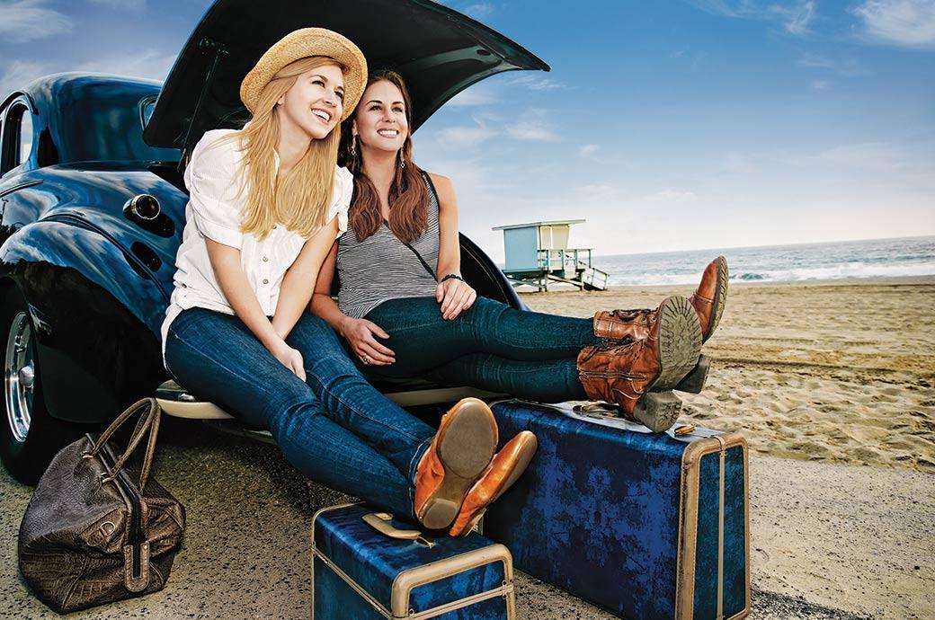 Dos muchachas que se sientan en el baúl de un auto por la playa con su equipaje listo para viajar